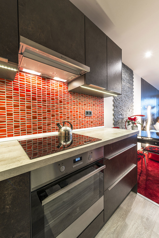 Kuchyňu spája s obývačkou jedálenský stôl pri kamennom obklade steny. V interiéri sa objavujú červené akcenty na doplnkoch, ktorým kraľuje koberec.