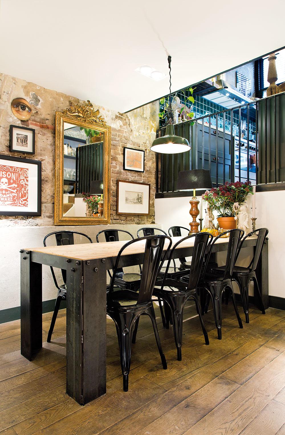 """OTVORENÁ KUCHYŇA ústi do jedálne, ktorá voľne prechádza do dlhej chodby. Starú """"obnaženú"""" tehlovú stenu zjemňujú obrazy, zrkadlo vstarodávnom ráme či originálne maľby na tanieroch."""