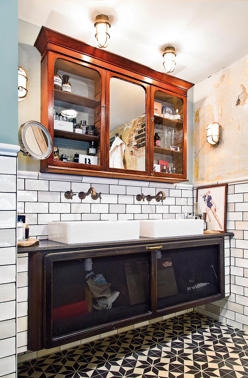 OPROTI VANI sú na starej zreparovanej skrinke položené dve hranaté umývadlá. Čierno-bielu farebnosť miestnosti spestruje hnedá visiaca policová skrinka so zrkadlom, ako inak, starožitná. Avšetko to pekne dopĺňajú továrenské svietidlá či staro pôsobiace armatúry.