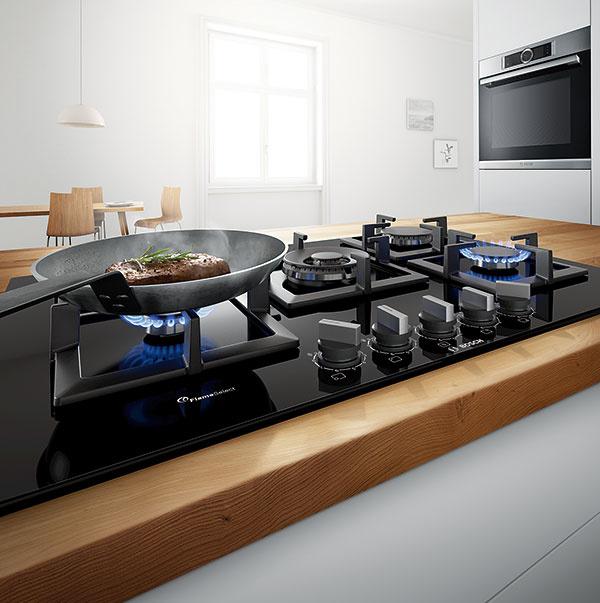 Plynová varná doska Bosch PPQ7A6B20 je jedným zmála plynových panelov, ktorých stupeň ohrevu možno presne regulovať vdeviatich stupňoch. Pri inštalácii máte možnosť výberu medzi zapusteným avystupujúcim zabudovaním. Okrem klasických štyroch horákov má aj tzv. wok horák svýkonom až 4 kW, povrch dosky je ztvrdeného skla, čo uľahčuje jej čistenie. Rozmer 56 × 48 cm, cena 629 €. www.bosch-home.com/sk