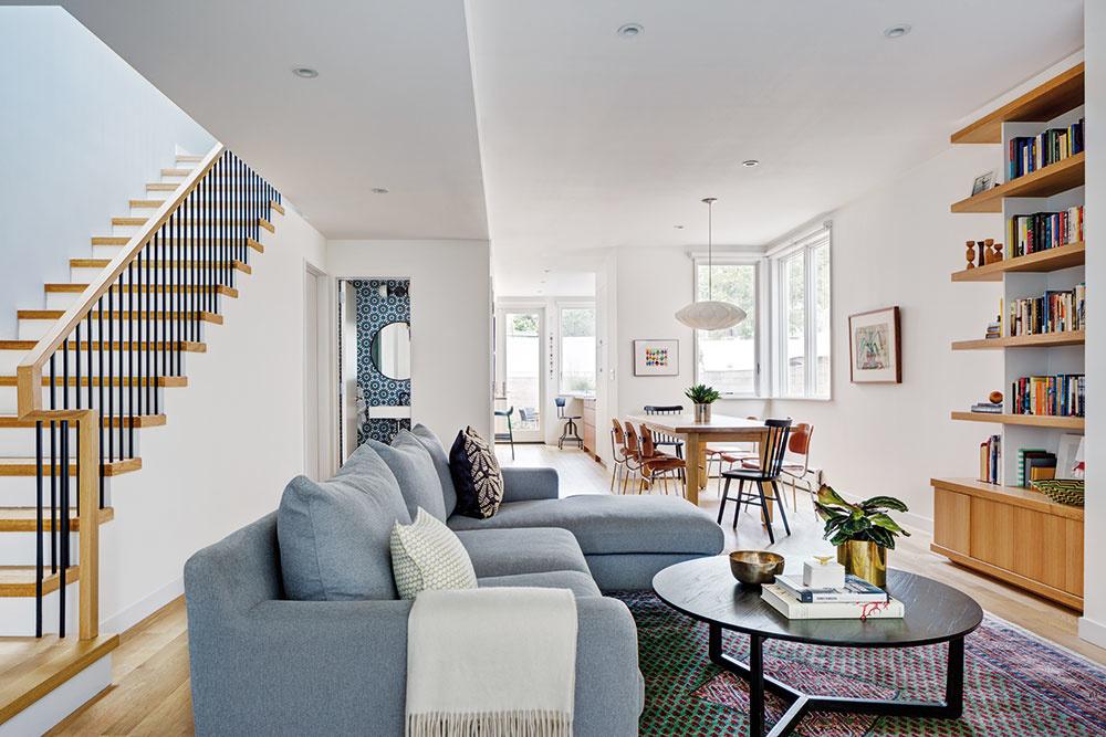 Presunuté schodisko. Aby mohli architekti dopriať uličnej fasáde viac skla aotvorenosti atým aj obývačke viac svetla, presunuli schodisko kbočnej stene. (Pohľad cez denný priestor smerom do záhrady.)