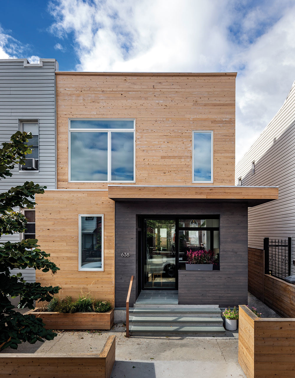 Rôzne odtiene dreveného obkladu opticky členia fasádu adodávajú jednoduchej stavbe na hravosti azaujímavosti. Farebné odlíšenie zároveň naznačuje inú funkciu či hmotové odľahčenie.
