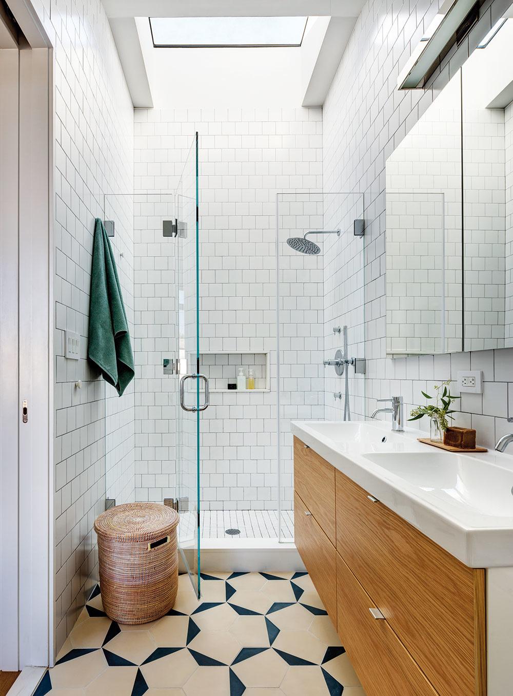 Pokojnú, nie však nudnú atmosféru dodáva hlavnej kúpeľni biely obklad asvetlá geometrická dlažba. Ani tu nechýba drevený prvok – má podobu čela umývadlovej skrinky.