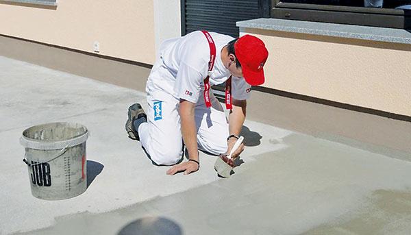 Na celú plochu cementového poteru naneste murárskym štetcom prvú vrstvu hydroizolačnej hmoty, ktorú dobre votriete do betónového podkladu.