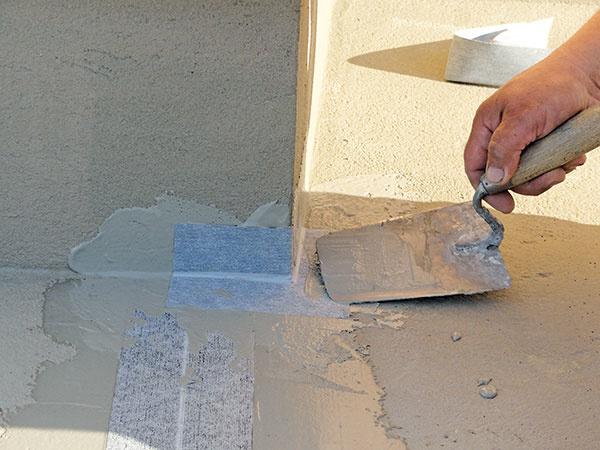 Vkútoch arohoch naneste izolačnú hmotu maliarskou špachtľou vhrúbke približne 1mm aosaďte do nej tesniace rohové prvky.