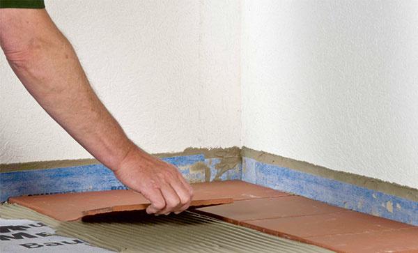 Po vytuhnutí tmelu pod izolačnou fóliou (potrebný čas závisí od použitého materiálu), môžete začať sukladaním dlaždíc do lôžka zlepiaceho tmelu.