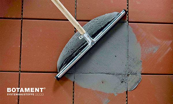 Keď je položená dlažba pochôdzna (potrebný čas závisí od použitého lepiaceho tmelu), nasleduje vyplnenie škár medzi dlaždicami škárovacou hmotou.