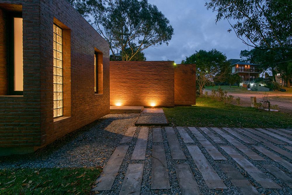 Tehlový jednopodlažný dom, ktorý sa hrá so svetlom