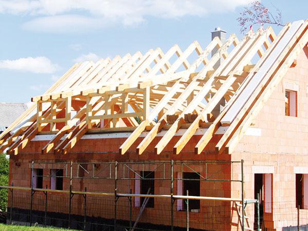 Pohľad na dom s hotovou konštrukciou krovu