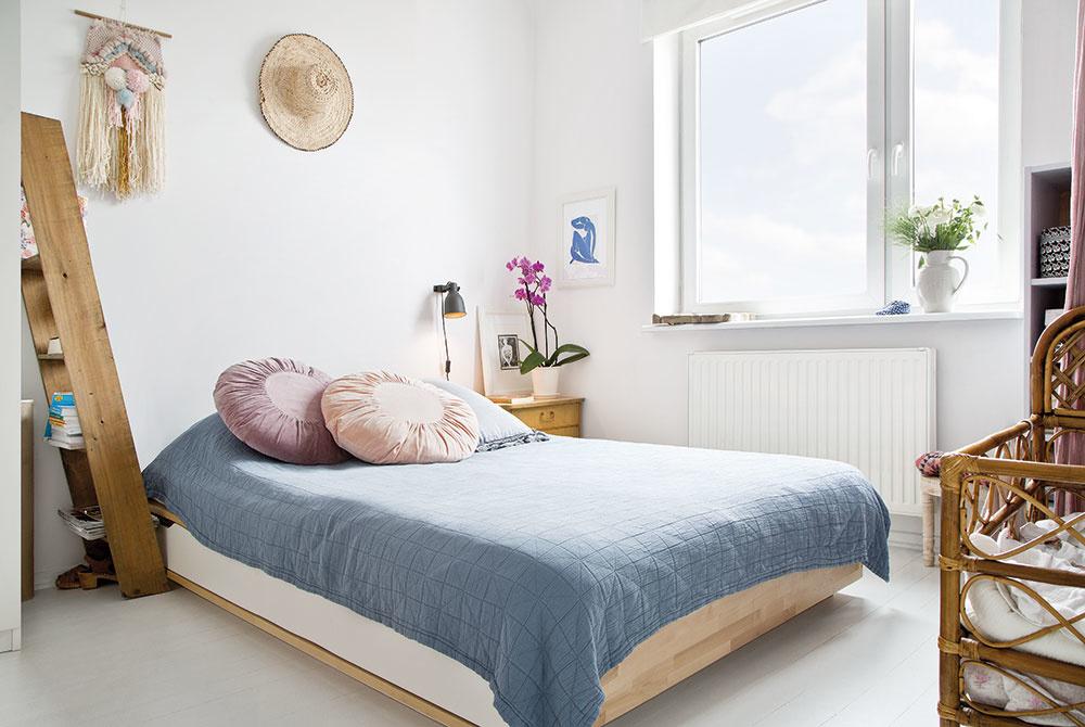 Aj spálňa, vktorej prevláda prevažne biela farba vkombinácii sdrevom, dýcha rodinnou atmosférou. Doplnky vpodobe okrúhlych vankúšov na posteli či živých kvetov ešte očosi viac podčiarkujú útulný ráz celej miestnosti.