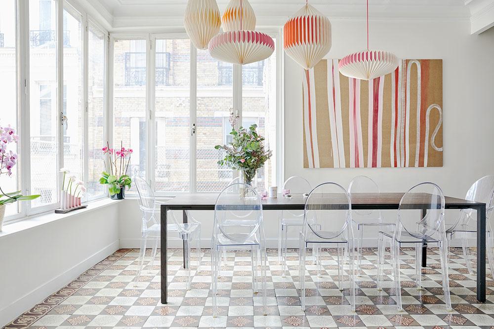 """IKONICKÉ STOLIČKY zpriesvitného plastu dokonale podčiarkujú vzdušnosť apresvetlenosť celého jedálenského priestoru. Jediným """"naoko"""" pevným bodom je dlhý tmavý stôl amožno ešte obraz na stene."""