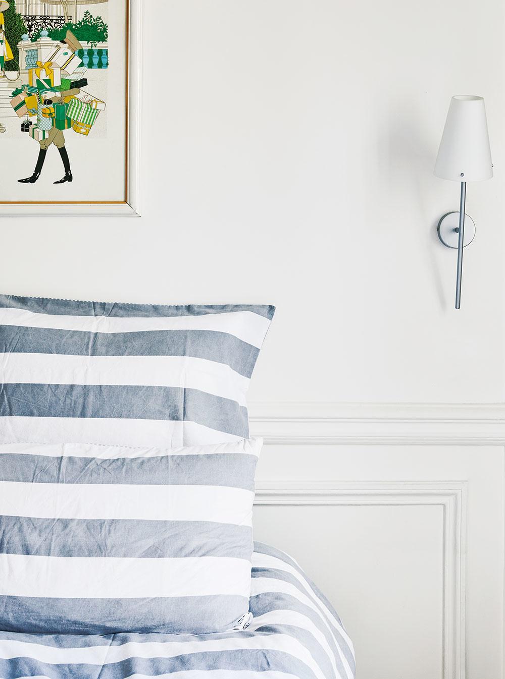 """SPÁLŇA sa nesie v duchu minimalizmu. Striedmu bielo-sivú farebnú kombináciu """"rozbíja"""" farebný obraz za čelom postele."""