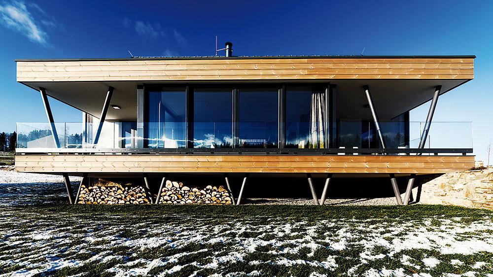 CELKOM ODLIŠNÝ POHĽAD ponúka dom zo svojej južnej strany. Terasa, ktorú architekt šikovne zasadil do svahu, pôsobí ako celkom nezávislý objekt. Zároveň použité materiály korešpondujú scharakterom okolitej prírody.