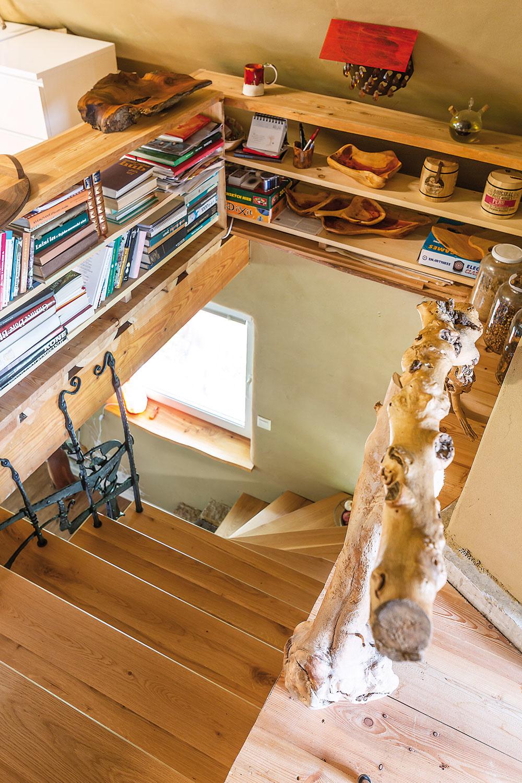 Malá knižnica na poschodí, sčasti lemujúca schodiskový otvor, zároveň funguje ako zábrana pred krokom vedľa.