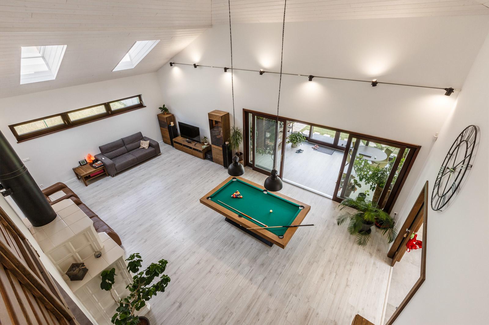 Spoločenský priestor otvorený až po krov si žiadal presvetliť aj cez strechu. Spolu so zimnou záhradou tak pár strešných okien pomáha privádzať do priestoru dostatok denného svetla. Vzhľadom na výšku ich umiestnenia sú vybavené systémom VELUX INTEGRA®, ktoré umožňuje diaľkové otváranie okien i markíz.