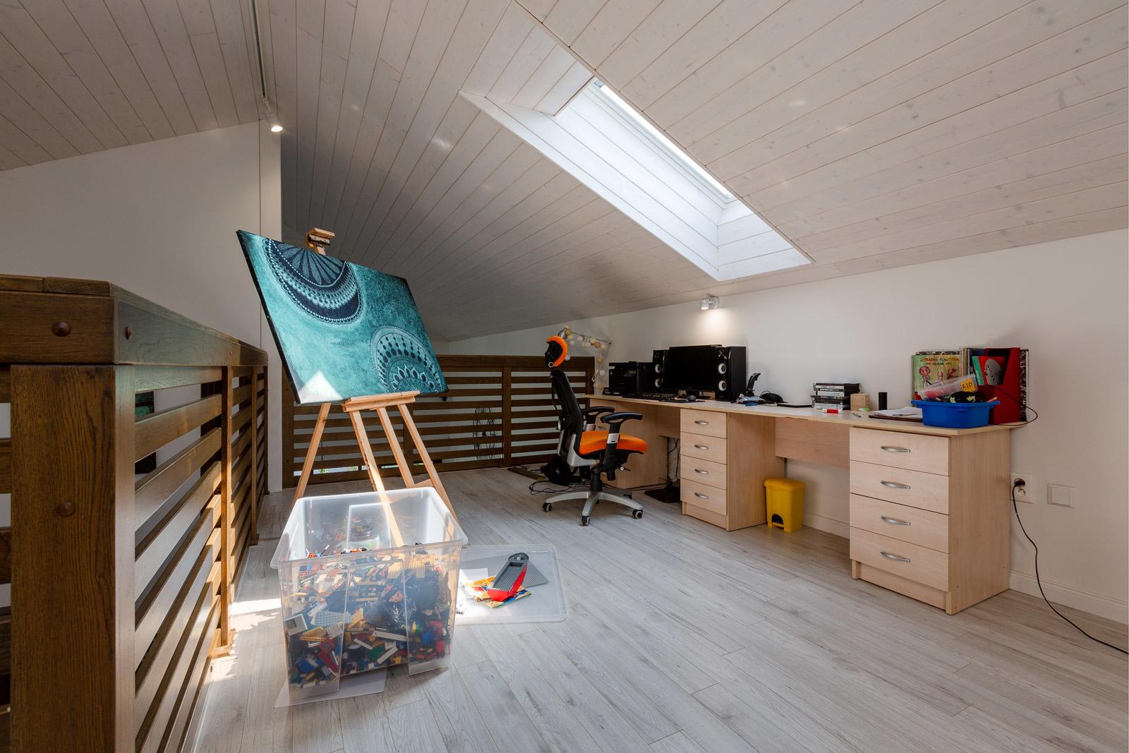 Jedinou miestnosťou na poschodí je malá pracovňa s výhľadom do obývacej izby. Dostatok denného svetla a čerstvého vzduchu tu zabezpečuje strešné okno VELUX.
