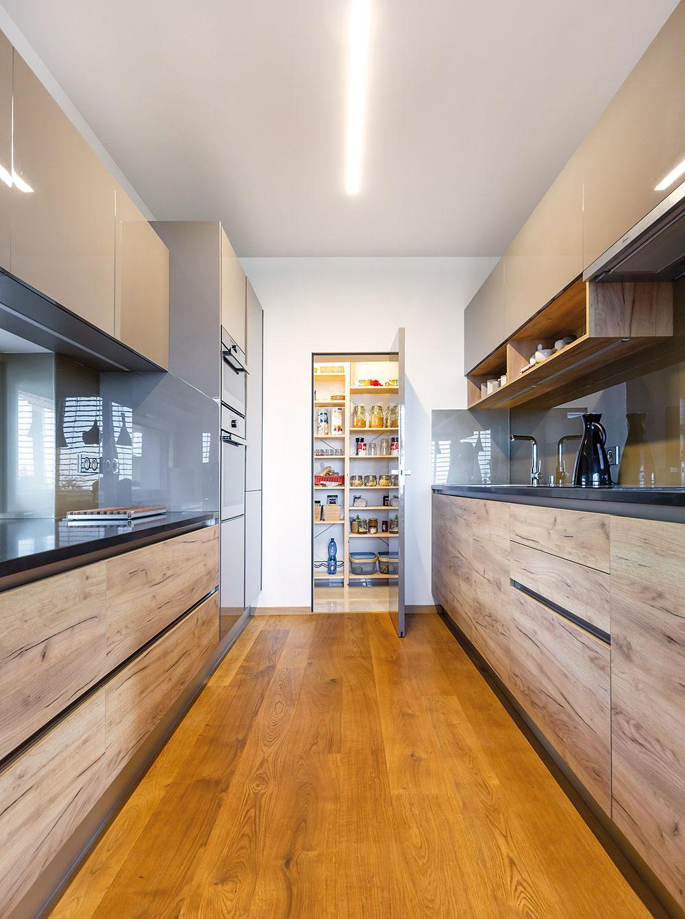 """SÚČASŤOU KUCHYNE je aj špajza sprehľadným dreveným policovým systémom, ktorá slúži nielen na uskladnenie potravín, ale aj na """"ukrytie"""" bežného drobného neporiadku, ktorý tak často """"zdobí"""" nejednu štýlovú kuchynskú linku."""