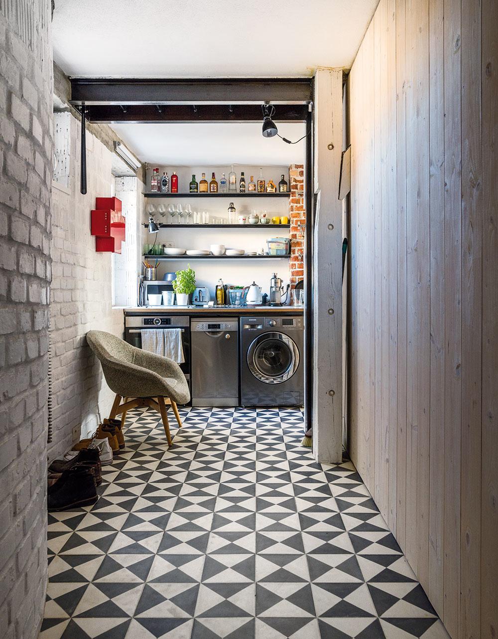Najväčší z bytov zahŕňa aj najdlhšiu chodbu – je to daň za samostatný vstup pri daných priestorových limitoch. Architekti v nej však zabránili nude materiálovou pestrosťou povrchov (pôvodnú tehlu a nové drevo tu dopĺňa pôsobivá ručne robená cementová podlaha). V rámci možností využili chodbu aj prakticky, na odkladacie priestory a umiestnenie kuchyne.