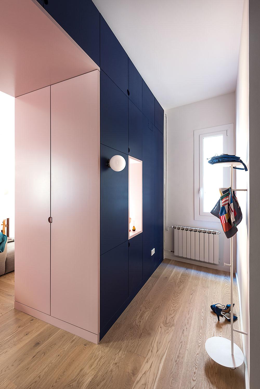 Tmavomodrý blok zároveň vytvára vo vstupnej časti praktický šatník. Aj svetloružové panely, ktoré lemujú priechod do obývačky, sú vlastne dvere skrine.