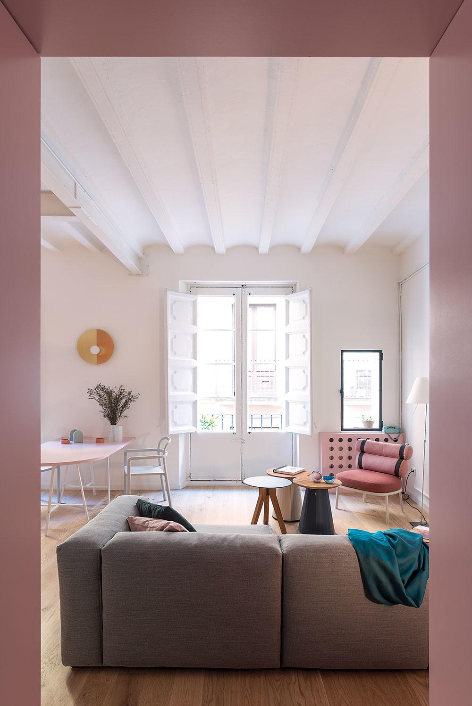 Pohľad zpredsiene do obývačky. Pri rekonštrukcii strhli falošný strop aobjavila sa katalánska rebierková klenba sdrevenými trámami. Architekti ju nechali natrieť nabielo, aby maximálne podporili svetlosť interiéru.