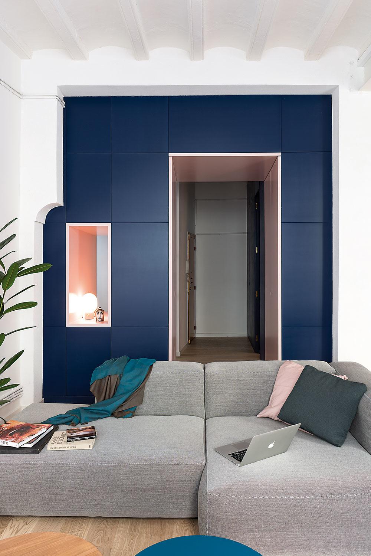 Pohľad zobývačky do predsiene. Dennú zónu oddeľuje od vstupnej časti bytu tmavomodrý blok súložnými priestormi. Do obývačky sa cezeň vchádza otvoreným priechodom.