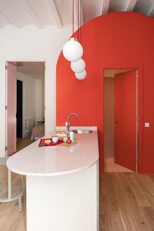 Svetloružové dvere vedľa kuchyne vedú do spálne majiteľky, ktorá je od zvyšku bytu izolovaná aposkytuje potrebné súkromie.