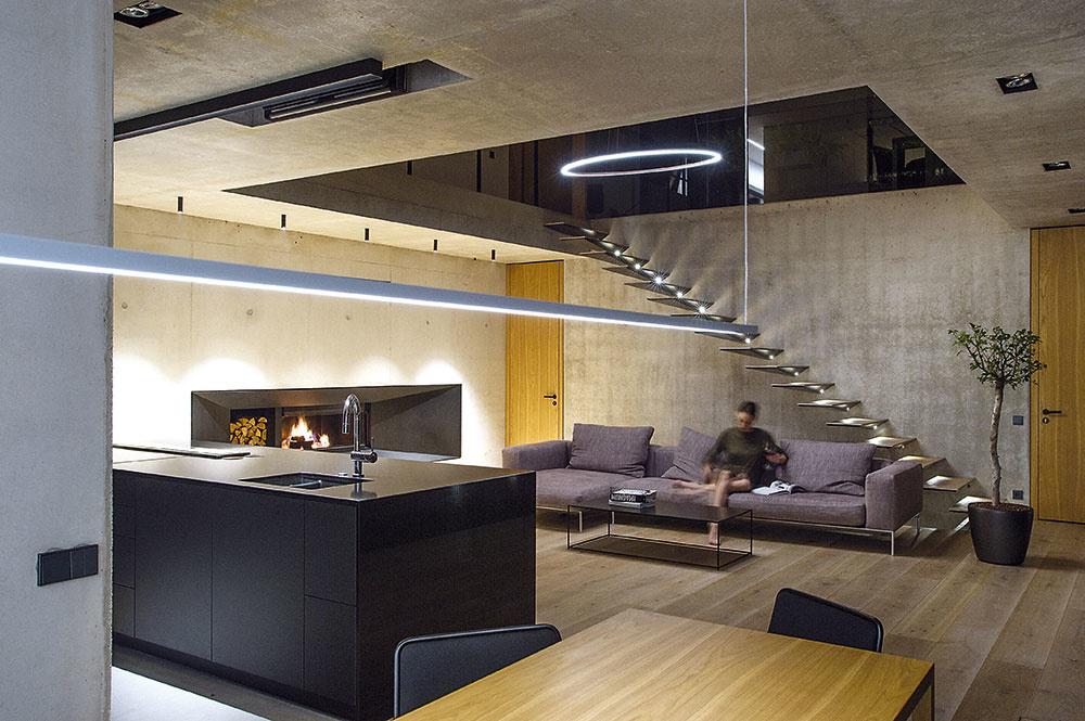 Rafinovaná jednoduchosť astarostlivý výber materiálov sú základné znaky interiéru celého domu. Pocit útulnosti apohodlia navodzuje dubové drevo na podlahách či oheň horiaci vo veľkom kozube. Prispieva knemu aj koncept osvetlenia, ktoré možno ovládať cez smartfón – kombinuje skryté prvky inštalované vstenách slíniovými svietidlami aumožňuje vytárať rôzne svetelné scény.