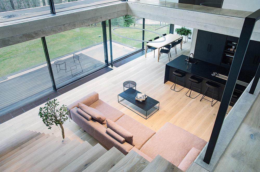 Obývačka sa otvára až do horného podlažia. Po efektnom schodisku sa vychádza na vnútornú betónovú galériu, zktorej je prístupná pracovňa ahlavná spálňa sterasou.