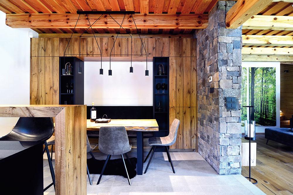 HRANICU medzi kuchyňou ajedálňou tvorí barový pult, pri ktorom si majitelia môžu vychutnať raňajky. Na bohatšie hodovanie sa využíva jedálenská časť smasívnym stolom snepravidelne opracovanými hranami, ktorú opticky prehrievajú zamatové stoličky akoža na zemi.