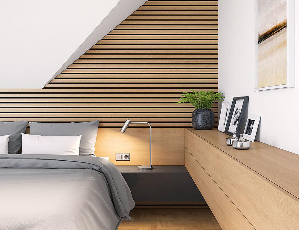 Obklad z drevených hranolov za posteľou príjemne zútulňuje celú spálňu. Tým, že šikmá časť zostala biela, priestor pod zníženým stropom pôsobí príjemnejšie.