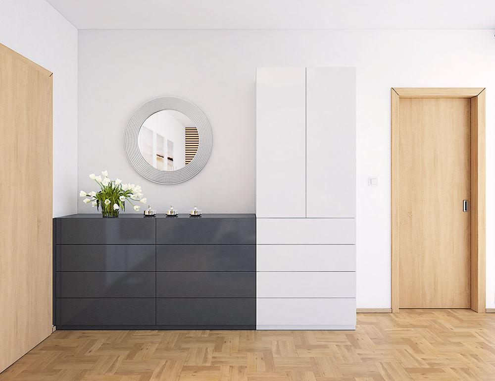Kombinácia dvoch farieb nie je náhodná. Kým tmavosivá nízka komoda selegantným zrkadlom na seba priťahuje pozornosť, biela skriňa zámerne splýva so stenou. Ukrýva vsebe žehliacu dosku, ktorá sa do jej útrob jednoducho aelegantne schová, keď je všetka práca dokončená.