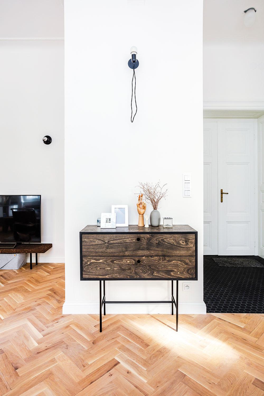 Nástenné lampy sú variáciou na atypické svietidlá navrhnuté Sašinou sestrou, architektkou Danielou Polubědovovou. Komoda skovovou podnožou atelom zbrezovej preglejky napustenej tmavým voskovým olejom  je vyrobená na mieru.
