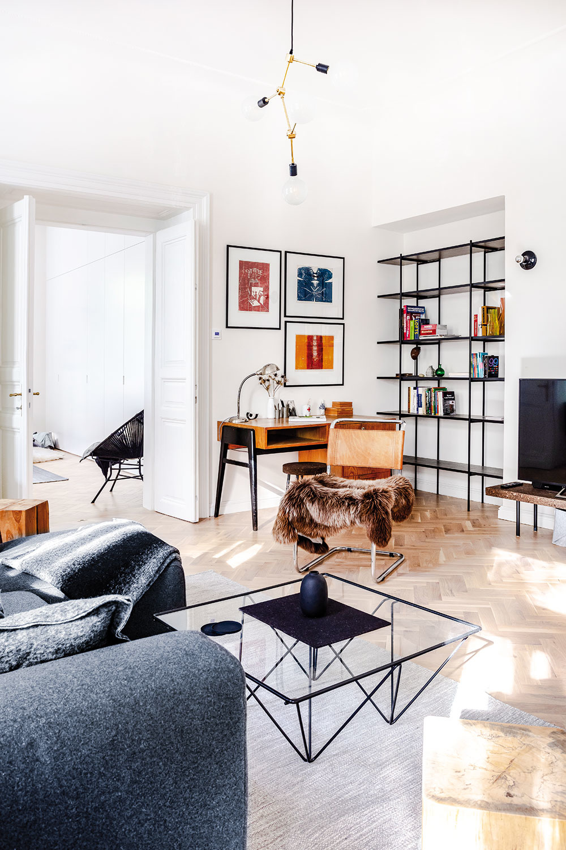 """Obývačka sa kúpe vzáplave denného svetla. Vďaka starostlivému návrhu osvetlenia však aj po zotmení vynikne starý písací stôl, kovový regál, ktorý navrhla autorka realizácie, či typické """"bauhausovské"""" kreslo srúrkovou konzolovou konštrukciou akoženým poťahom od architekta Marta Stama."""