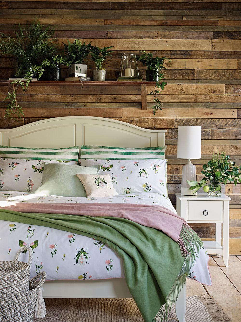 """Nemusí to byť práve drevený obklad na stene, ktorý má vypovedať o naturálnom charaktere interiéru (môže totiž pôsobiť veľmi ťažkopádne). Dostatočné """"sprírodnenie"""" vnesú do spálne aj obliečky s jemnými floristickými motívmi, ľan či bavlna a, samozrejme, živé kvety. Jednoduchý koncept, ktorý je založený na minime nábytku, neutrálnych zemitých odtieňoch, ktoré oživuje zelená farba so sviežim akcentom fialovej."""