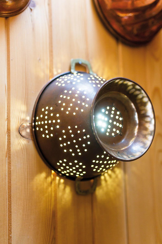 """Stenu pri schodisku vyzdobili domáci starými medenými nádobami. Nevedeli zohnať nástenné svietidlo, ktoré by sa sem hodilo. Za nápad použiť starý """"cedník"""" vďačí Natali kolegyni zpráce."""