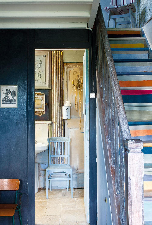 Farebné schodisko vedie kzrenovovaným spálňam vpodkroví. Každý schod namaľovala Annie iným odtieňom, aby ho rozžiarila.