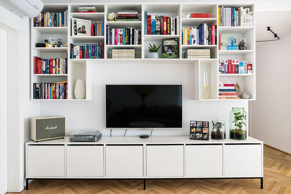 """Knižnicu, vktorej je zakomponovaný televízor, vylepšil Marek preňho typickou """"drobnosťou"""" – otvorené police netradične odsadil od skrinky vspodnej časti, čím vznikol ďalší úložný priestor. Biele skrinky skovovou podnožou sa tak zároveň dajú využívať napríklad aj ako """"párty sedenie""""."""