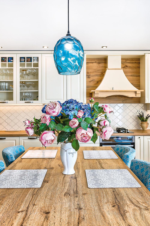 JEDÁLENSKÝ STÔL má rovnakú dosku, ako je tá pracovná. Čalúnené stoličky, ktoré sú očosi vyššie ako klasické, sú od slovenského výrobcu. Látku si vybrala majiteľka vjemnom modrom odtieni adoladila knej aj svietidlo.