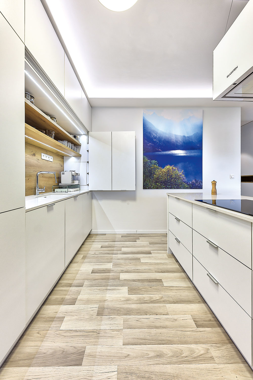 """Kuchyňa nemá zbytočne konkurovať stolu avytvárať rušivú dominantu spojeného priestoru. Je tvorená jednoduchým ostrovom so """"zakapotovaným"""" zaveseným digestorom asamotnou kuchynskou stenou, ktorá je navrhnutá tak, aby sa dala celá uzavrieť."""