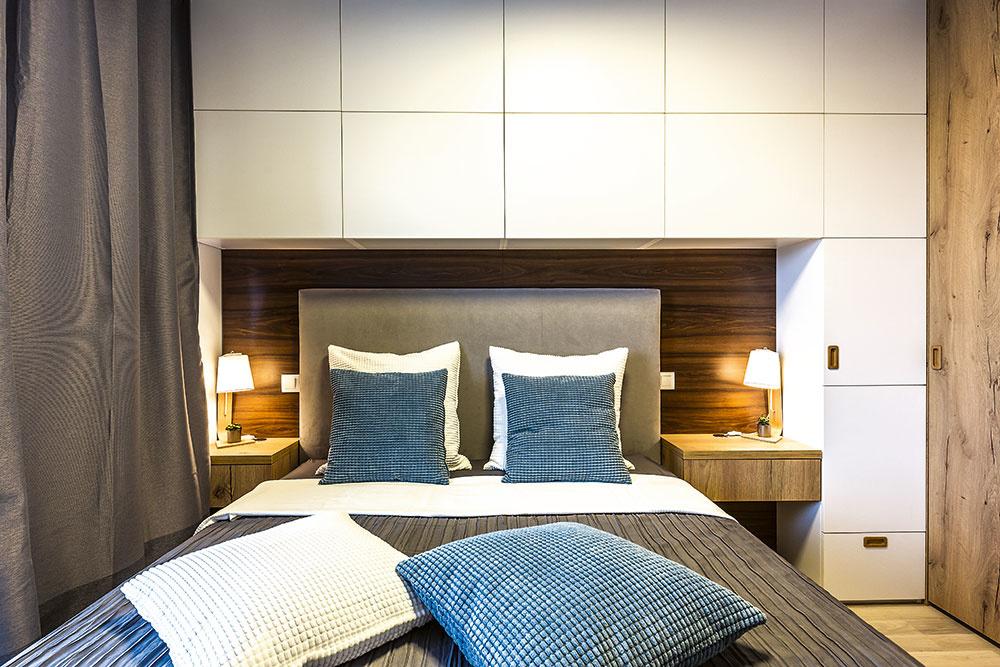 Na stene za posteľou je na mieru vyrobená šatníková skriňa snočnými stolíkmi azáhlavie postele tvorí drevený obklad, ktorý pôsobí teplo avytvára sbielou príjemný kontrast.
