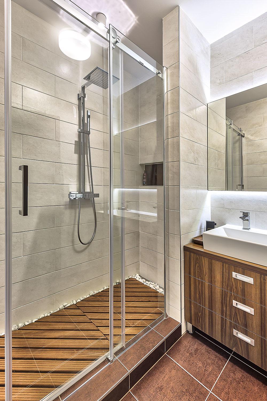 NAMIESTO vane majiteľ preferoval sprchovací kút. Na podlahe vňom je položené tíkové drevo apo okrajoch sú vysypané biele okruhliaky. Farebnosť je podobne decentná ako vo zvyšku bytu. Svetlá piesková kombinovaná shnedou.