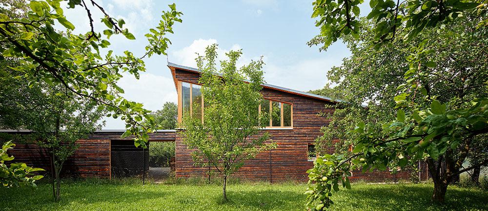 Krytý priestor medzi domom adielňou má niekoľko funkcií. Primárne tvorí chránený vstup do domu ijeho technickej časti sdielňou, ďalej slúži ako dreváreň avneposlednom rade je to malá odpočinková terasa na kávu.