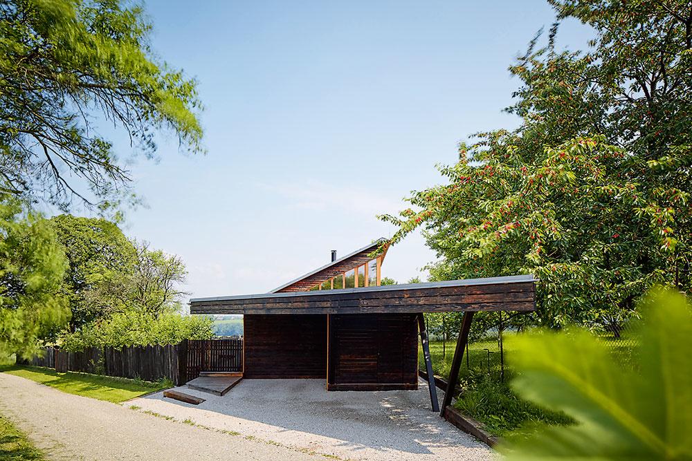 Dve časti domu – vyššiu, obytnú, anižšiu, vktorej je situovaná dielňa, prepája spoločná strecha. Prekrýva zároveň terasu, lemujúcu dom zo strany záhrady, aj priestor pred vchodovými dverami apred domom vytvára kryté státie pre dve autá.