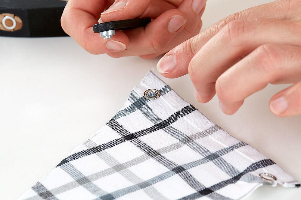 Plachtu uviažeme na krúžky (priechodky), cez ktoré neskôr prevlečieme motúz. Stačí použiť dva až tri krúžky.