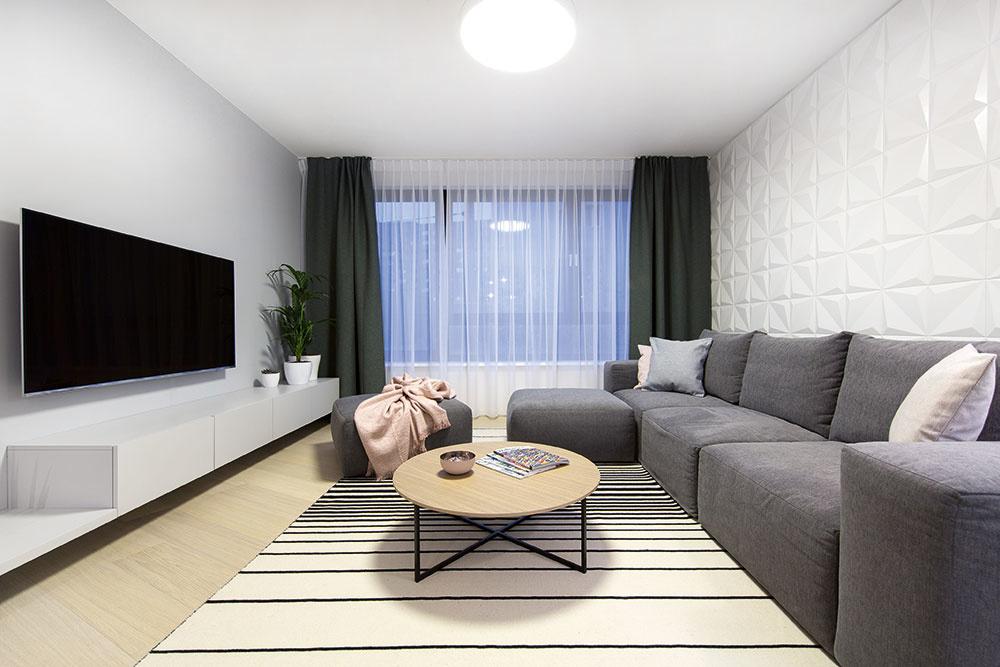 OBÝVACIA ČASŤ dennej zóny je zariadená látkovou sedačkou so samostatnou taburetkou a televíznou skrinkou, ktorá obsahuje miesto pre hifi komponenty. Keramická 3D stena za sedačkou vobývačke plní najmä estetickú funkciu, pričom vkuchynskej časti sa mení na funkčný prvok – kuchynskú zástenu.