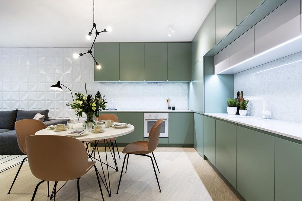 SKRYTÁ ŠPAJZA. Vkuchyni sú na prvý pohľad neviditeľné dvere do špajze, ktoré vyzerajú ako kuchynské skrinky. Vdennej zóne dominuje keramický 3D obklad, ktorý funguje vkuchynskej časti ako zástena, vobývacej zasa ako pozadie sedačky.