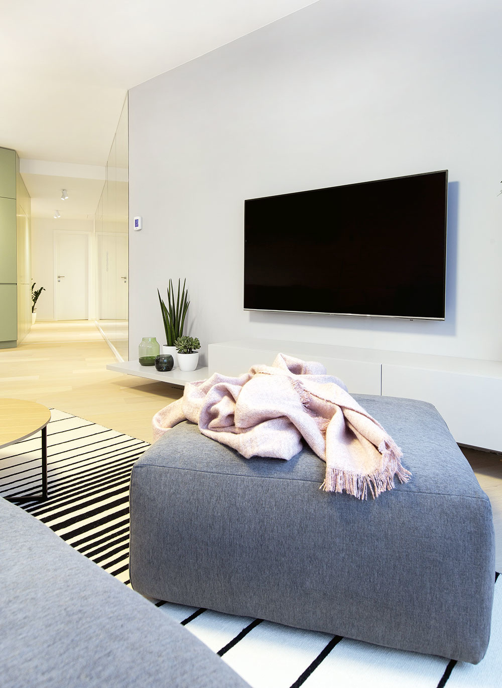 PRI MONOCHROMATICKÝCH STENÁCH asivej sedačke vyniká vobývačke drevená podlaha azávesy skobercami, ktoré dodávajú priestoru komfortný aútulný nádych.