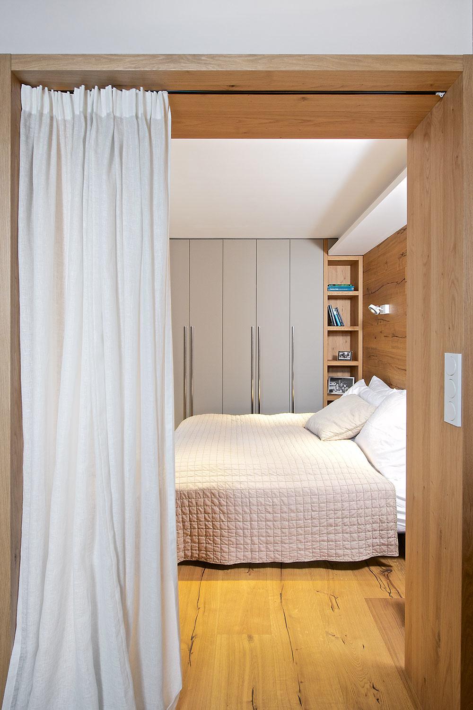 Spálňa je od denného priestoru oddelená skôr opticky – masívnym obložením dverného otvoru azávesom.