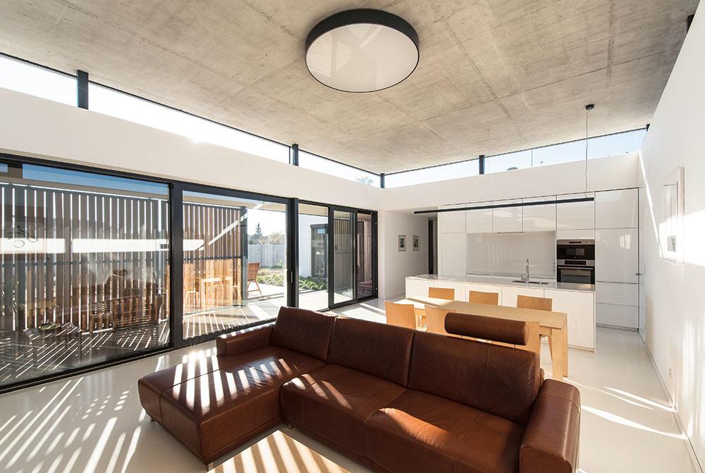 Hlavný obytný priestor tvorí spojená kuchyňa s jedálňou, sedenie s krbom a prístupom na krytú terasu. Zvýrazňuje ho levitujúca betónová stropná doska, ktorá spolu so svetlíkom, prebiehajúcim po celom jej obvode, vytvára v miestnosti priam chrámovú atmosféru.