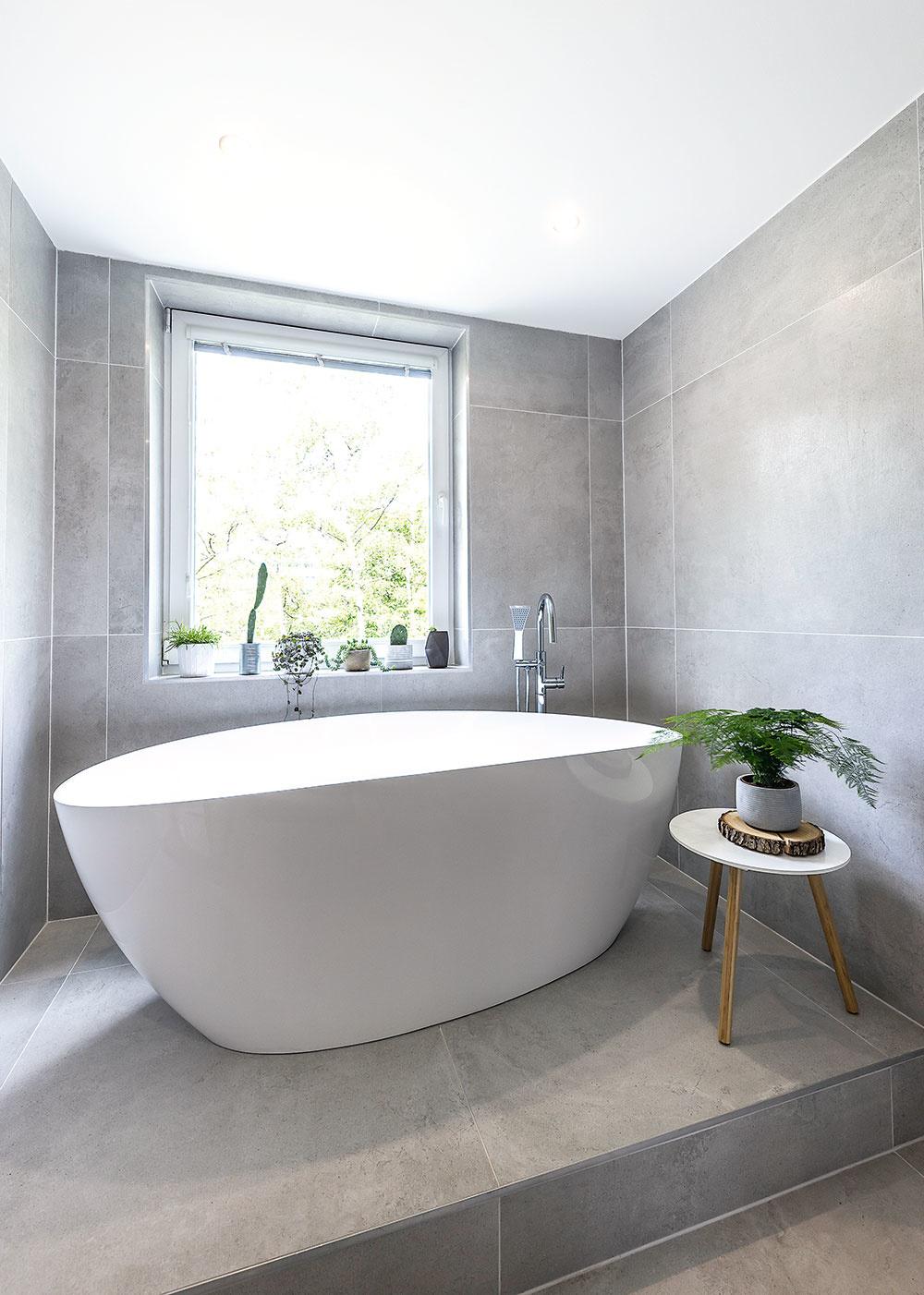 VOĽNE STOJACA VAŇA pod oknom priam nabáda oddychovať vo voňavom kúpeli. Aby dokonale vynikla, postavili ju na vyvýšené pódium atoto riešenie kúpeľňu aj pekne opticky predeľuje.